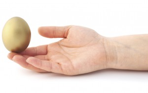 Isolated gold egg balanced on a finger. Balanced investment portfolio.